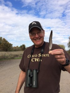 Biology professor Jay Bogiatto holds a Eurasian Wigeon feather.