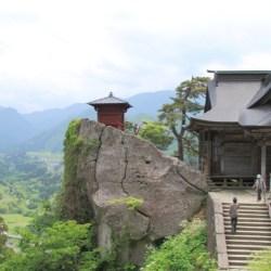 百丈岩にそびえる納経堂と開山堂。向こうには出羽の山々。