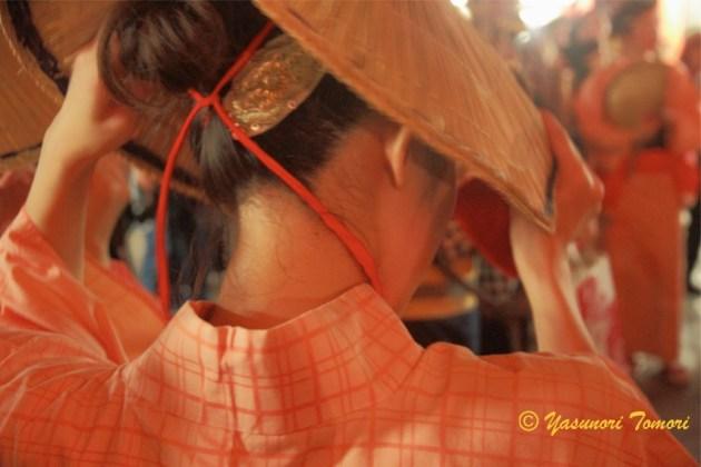編み笠を脱ぐ女性=浅草・浅草寺で行われた「おわら風の盆」にて