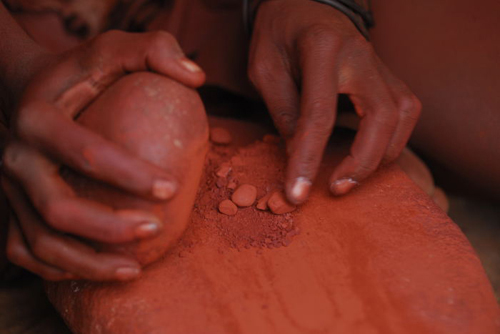 Himba woman grinding ochre into a fine powder