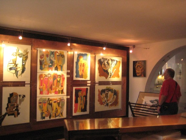Photo of Tony Zeoli looking at the original artworks for sale in the shop at Casa De Guayasamin