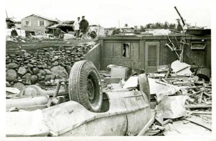 Dorothy West, mother of Tom West, and a friend wear coats to ward off the cool temperatures as they survey the damage the day after the tornado. The family's 1963 Chevrolet Impala Super Sport ended up on its top amid the rubble