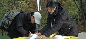 Susan Tsin, a volunteer with Citizen Scientist, helps a participant register for Rouge Valley's first-ever Eco Exploration.