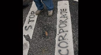 """Activist tags the slogan """"Stop Corporate Greed"""" along the side of the road."""