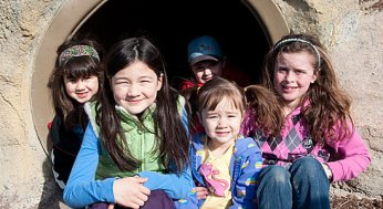 A group of children take a break from climbing through a tunnel at the Zoo for a photo opportunity
