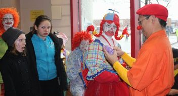 Colourfuly dressed clowns make balloon animals for kids at Winterfest.