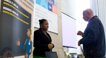 Kriss-Ann Cousley with the Ministry of Economical Development and Innovation discusses entrepreneurship with a parent.