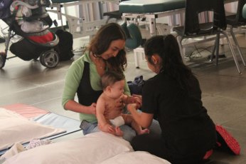 Baby Lyam gets a little fussy, so Fariba Golpsand holds him while Tiffany Quintos completes the massage