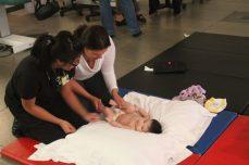 Leslie Supnet shows Priya Kumar some massage techniques for baby Sabrina