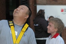 Stephen Chow, who is afraid of heights, looks up in awe of what he had just accomplished as the Easter Seals Ambassador looks on.