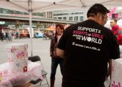 A Plan Canada employee sports his t-shirt while selling pink lemonade.