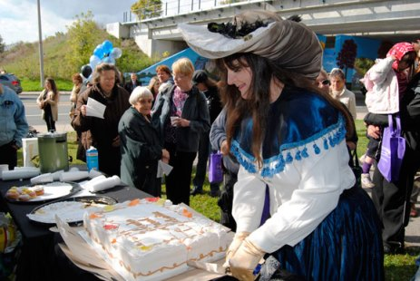 De Anne Lamirande cuts the cake at the Oct. 20 unveiling of the Warden Underpass Mural, which she and her team painted.