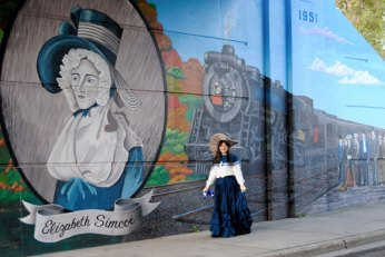Artist De Anne Lamirande, dressed as Elizabeth Simcoe herself, stands by the portrait of Elizabeth Simcoe.