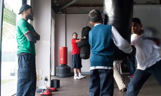 Coach Daron observes some of his youth hit the punching bags.
