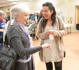 """Jessica Bundy, right, shares a smile with one of the guests. In addition to having art on display, she performed her song, """"My Body Instead,"""" during the night."""