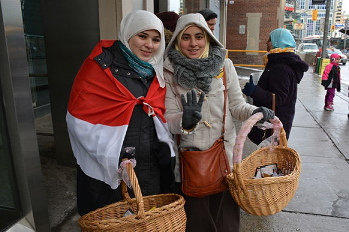 Asmaa Ellithy and Rania Abdelhady help distributing cards with portraits of martyrs, every card is attached with a small chocolate.
