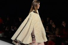 Lace sleeves pop out of a textured cape.