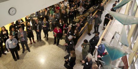 Attendees listen to speeches and mingle.
