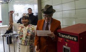 Moe Angelos, standing on the right, is a volunteer who helps run the artists' newsstand at Chester station. She educated commuters with a performative history lesson about the Bloor subway line.