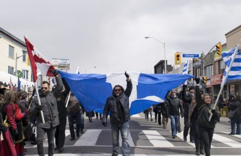 The final marchers. A group of men and women hold a giant Greek flag over their heads to celebrate the end of the parade.