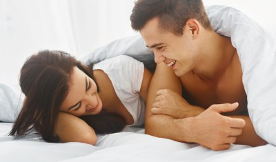 Close up portrait of romantic young man and woman in bed at home. Relationships, love, closeness.