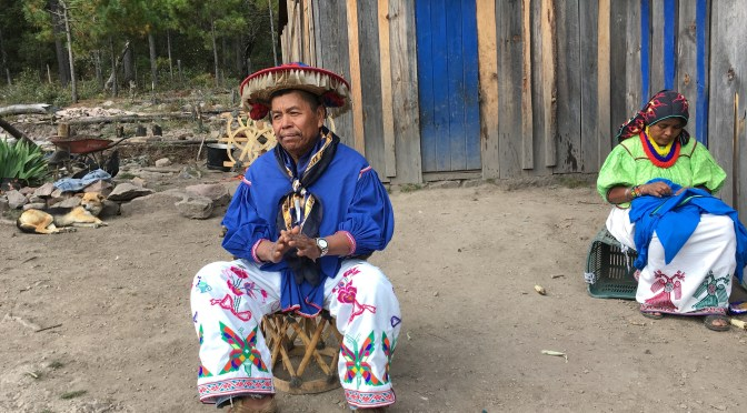 Juventino Carrillo, a former authority of the Huichol community of San Sebastian Teponahuaxtlán, discusses the long history of the land disputes as his wife, Marta Torres, sews the family's traditional clothing. Thomson Reuters Foundation/Nelson Denman