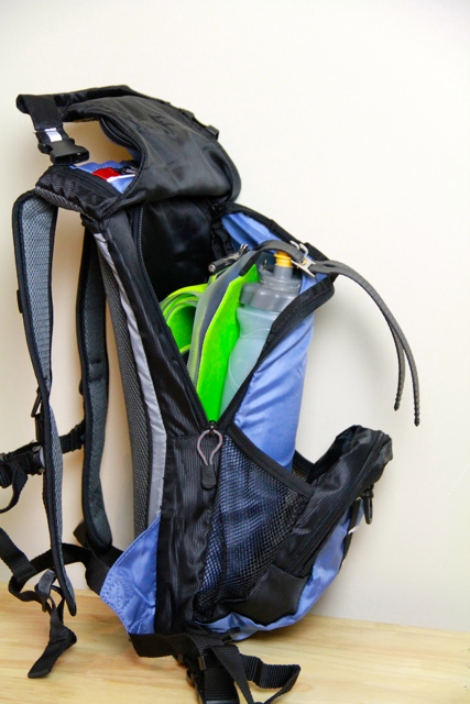 picture of Outdoor Product Ripcord backpack from side with ski skins and water bottle in zippered area