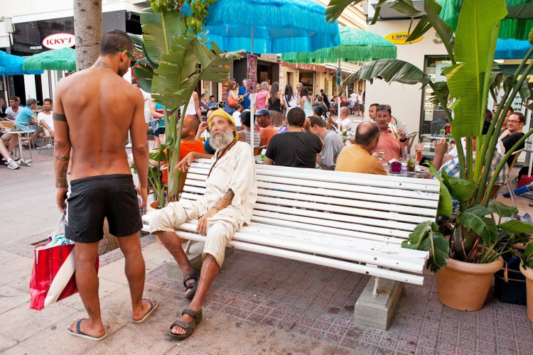 """Sitges, Spain - August 21, 2012: A shirtless man returning from the beach stops to talk to a man on a park bench."""