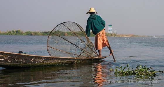 An Intha fisherman outside the Inle Lake canal leading to Nyaungshwe. The Intha have a unique way of paddling their boats with their feet