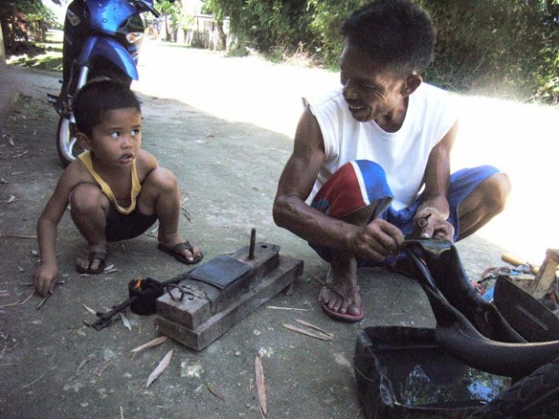 A repair man fixes my flat tyre at Siquijor, Philippines. Photo: TravelingReporter.com
