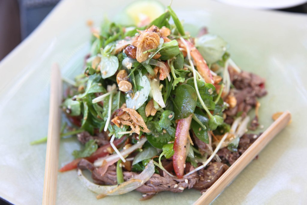 Goi Bo- Lime marinated beef salad, morning glory, tomato, onion, Nam Hai garden herbs