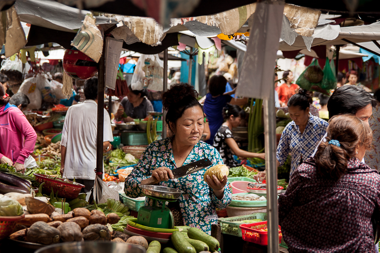A seller cuts off a slice of a fruit in the market