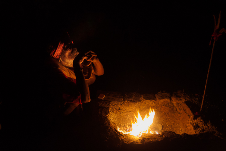 The Sadhu, who lives atop the fort, warms himself by the fire