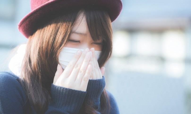 花粉症でくしゃみが止まらないマスクをした女性