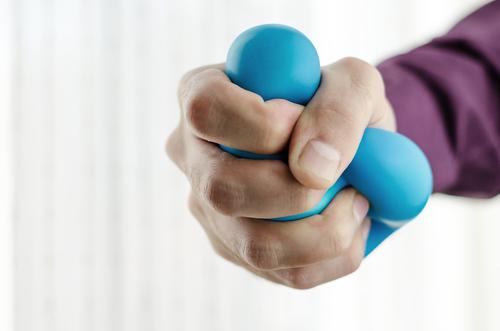 Hand crushing a stress ball