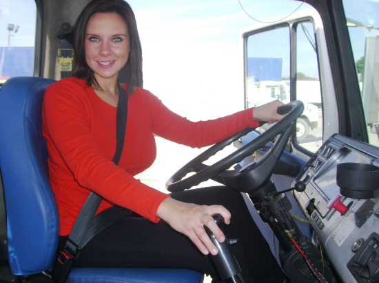 Image of a young woman in a bright red sweater driving a semi tractor trailer she has long brunette hair and a nice smile, she is facing the camera and she is very attractive