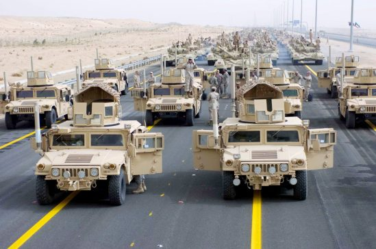 Photo Credit: Third Army PAO A formation of armored vehicles, manned by U.S. Army and Marine Corps personnel, stand ready to lead a convoy of coalition forces through the parade grounds established for the 50/20 celebration in Kuwait, Feb. 21.