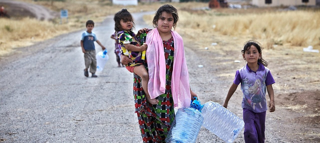 """""""An Iraqi woman from Mosul holds her daughter in one hand and empty water containers in the other. Two other children follow her in search of water near the Garmava temporary camp, where UNHCR has delivered tents. Getting food and water is a challenge."""