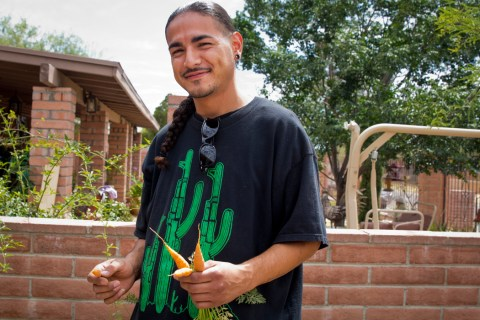 Jesus Romero, 26, a co-founder of Flowers and Bullets, with carrots that he grew in his yard.