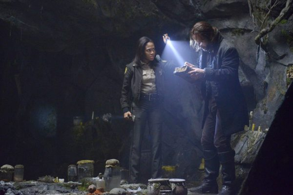Ichabod and Abbie examine George Washington's bible in a cave on Sleepy Hollow