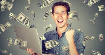 Successful man using laptop building online business making money