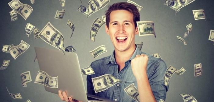 Successful man using laptop building online business making money