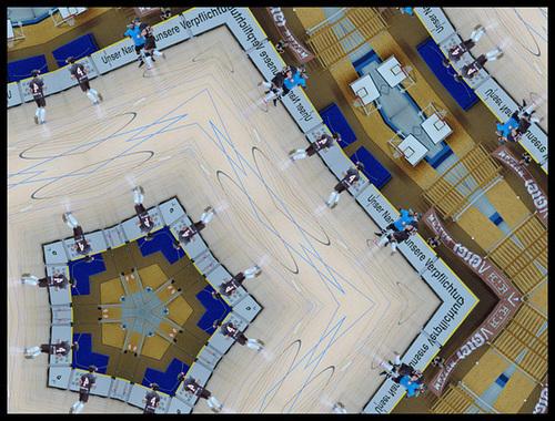 Das Spielfeld der Halle Budapester Straße mit einigen Spielern. Per Bildbearbeitung mehrfach auf einen virtuellen Würfel gespiegelt und danach noch ein wenig verzerrt, abgerundet und teilweise Spieler auf den Kopf gestellt. Ziemlich wirres Konstrukt, was sich nicht wirklich beschreiben lässt, lol