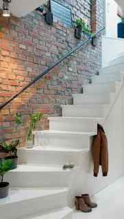 white staircase and rustic brick wall