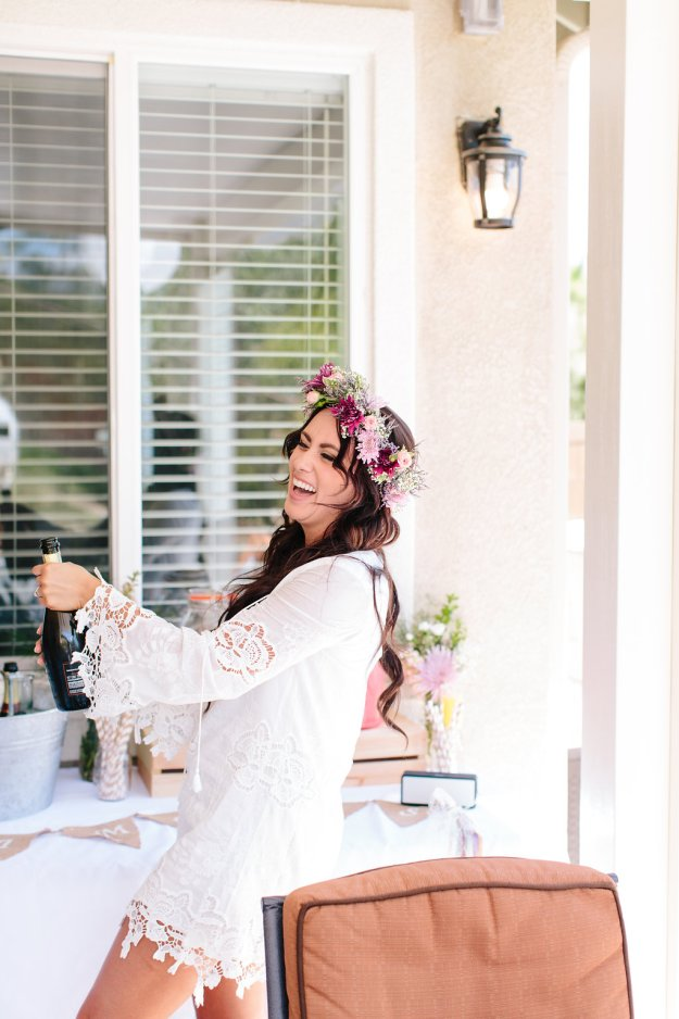 A Flower Crowns & Champagne Backyard Bridal Shower | Ultimate Bridesmaid | Dulcet Creative Bride popping champagne bottle