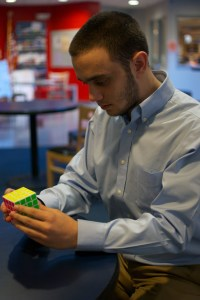 Freshman aerospace engineering major Joshua Bloch with a four-by-four Rubik's Cube at Mary- land Hillel. Amos Remer/Mitzpeh.