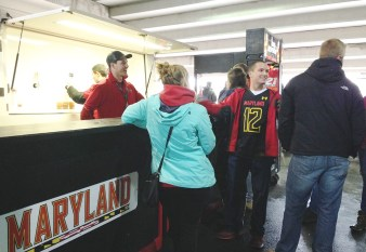 """Football fans at the Michigan game line up at a Byrd Stadium beer stand, which includes a sign saying """"Drink Responsibly,"""" to buy alcohol while an event staff member fills cups from a tap. Jacqueline Hyman/Mitzpeh"""