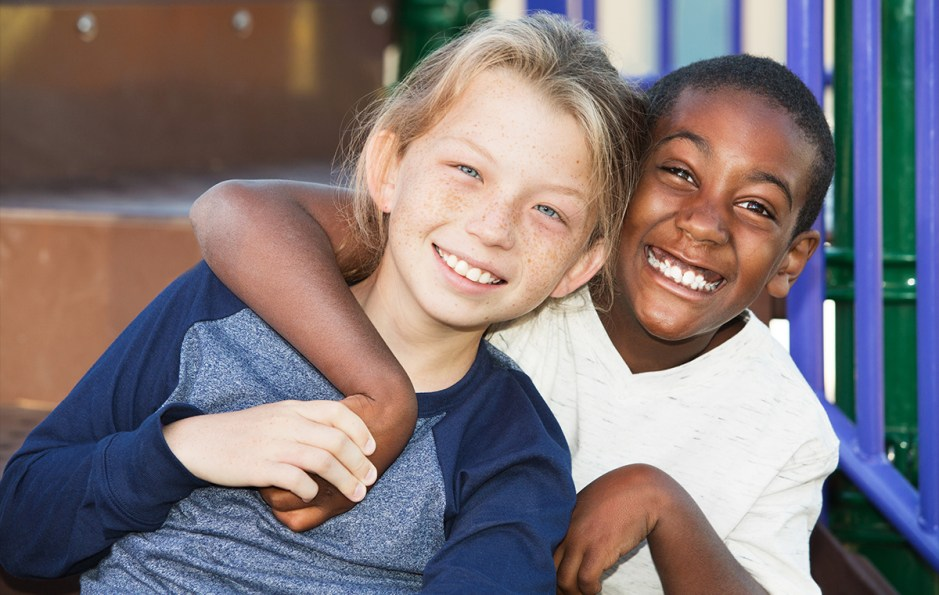 Happy African and Caucasian male child friends on playground set