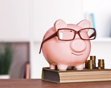 Piggy bank in glasses with book and coins on home or office background