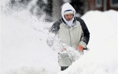 Justin Kidd appears lost in a snowbank as he snowblows his neighbor's driveway in Brigham City. (AP Photo)
